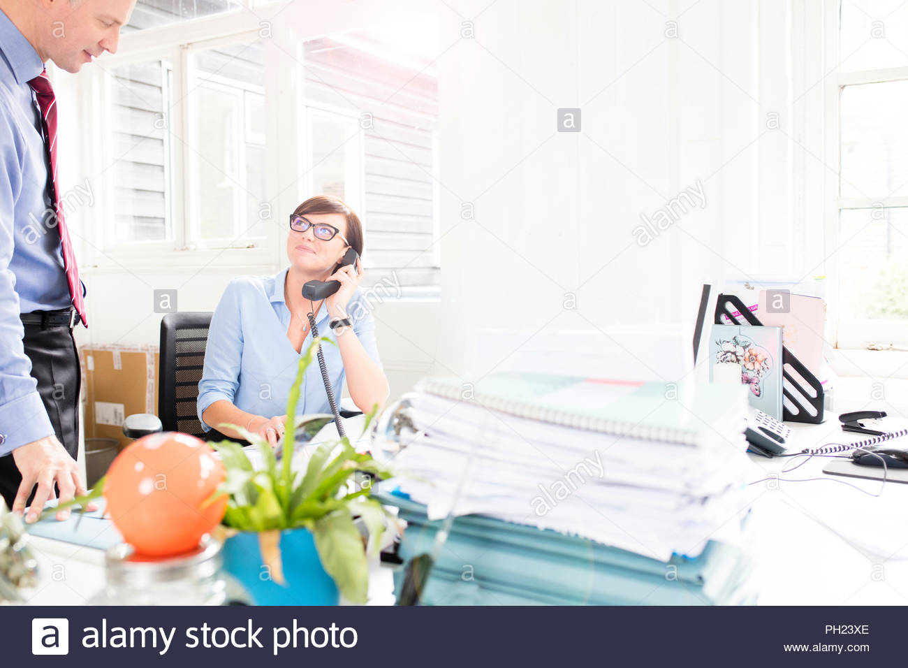 Businesswoman on phonecall listens to colleague in office - Stock Image