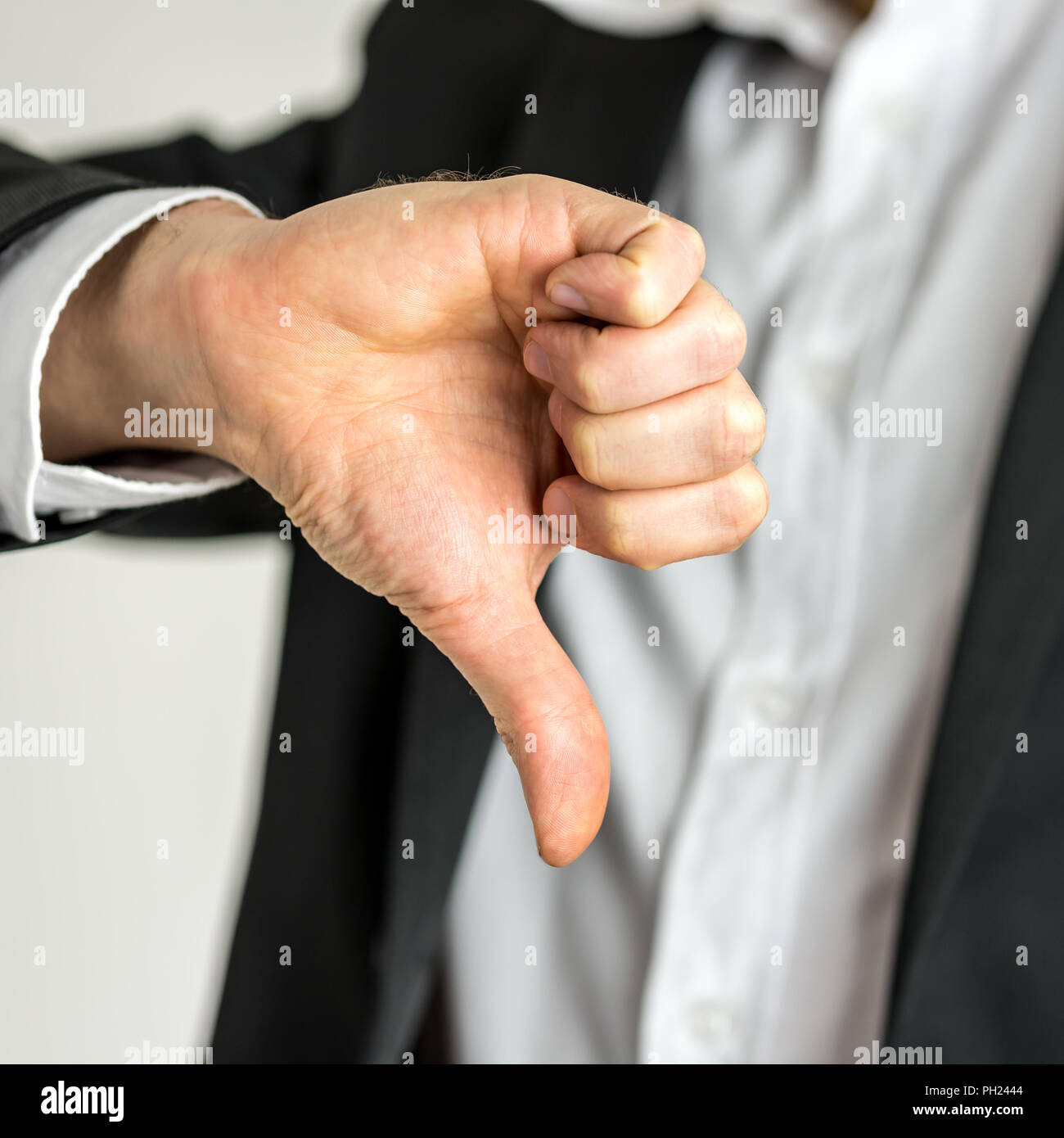 Man giving a thumbs down gesture of disapproval showing his negativity and dissatisfaction, close up of his hand. - Stock Image