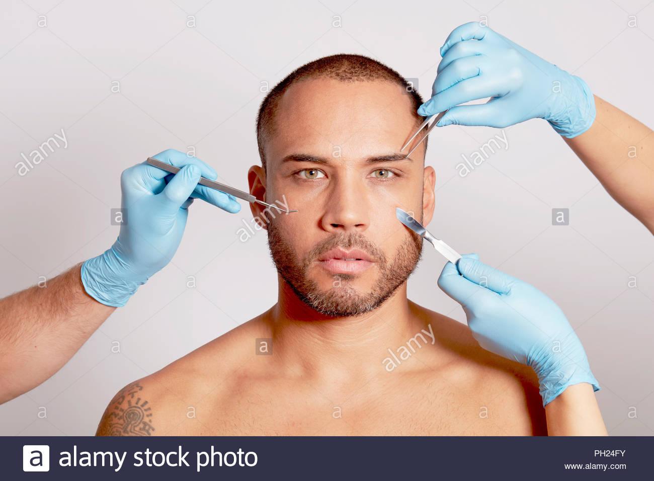 Mid adult man wearing moisturiser. - Stock Image