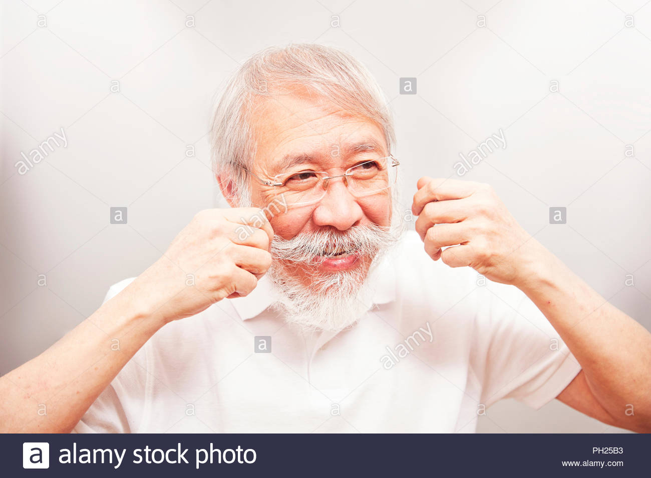 Senior man twirling his moustache - Stock Image