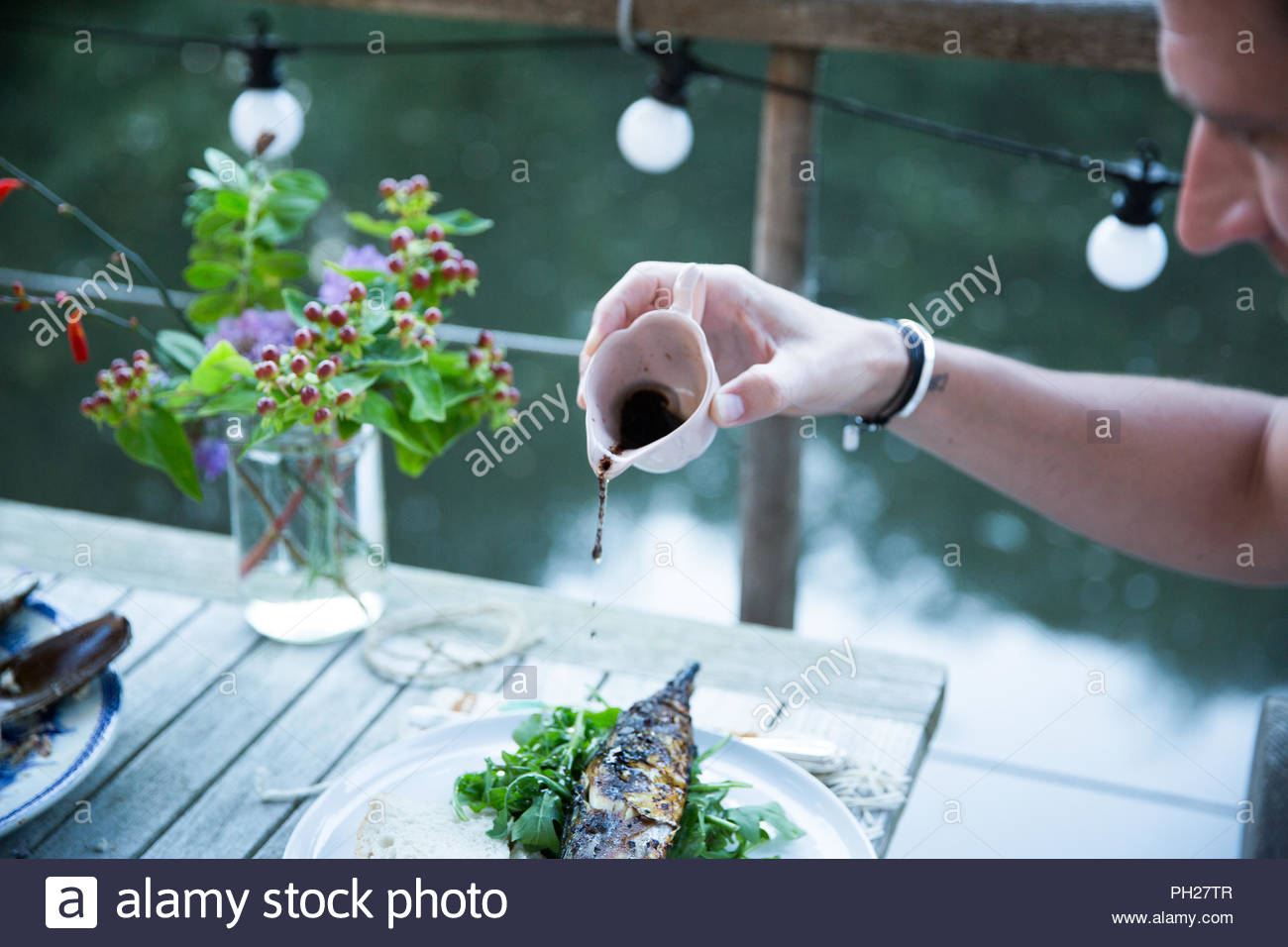Hand of man pouring vinegar onto grilled fish - Stock Image