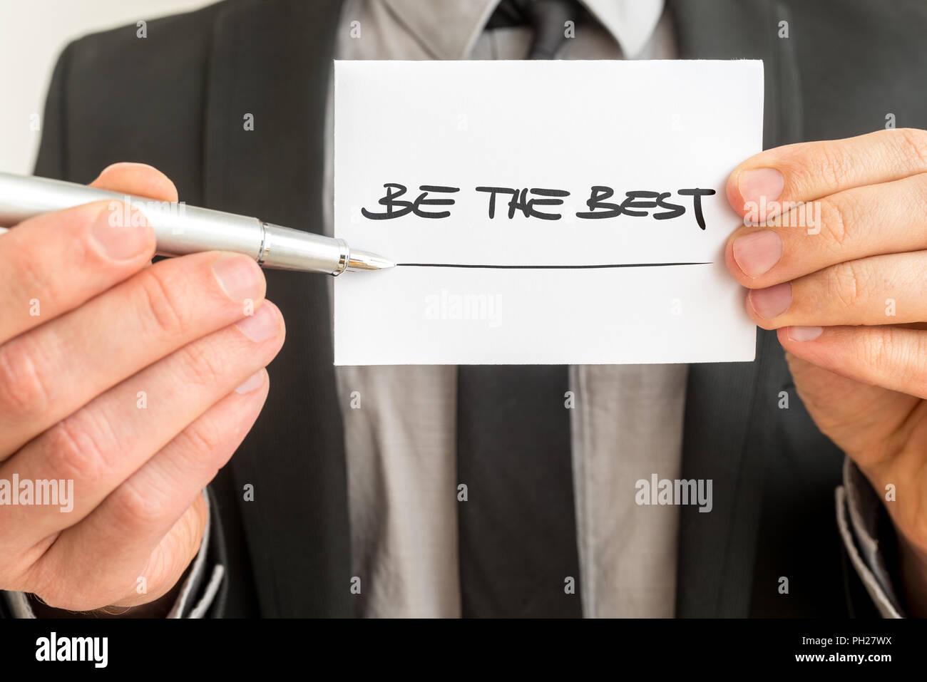 Closeup of personal therapist showing a white card with a Be the best sign encouraging you to live up to your fullest potential and realise your goals - Stock Image