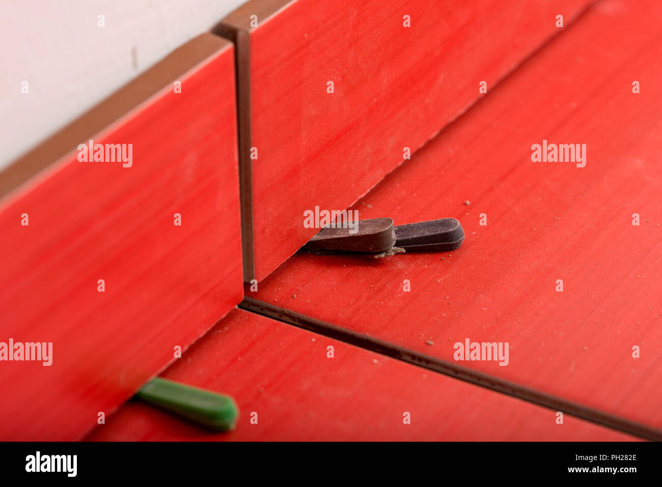 Close up view of bottom spacers used in tiling a wall to ensure an even gap for the grout between the tiles in a DIY and renovation concept. - Stock Image