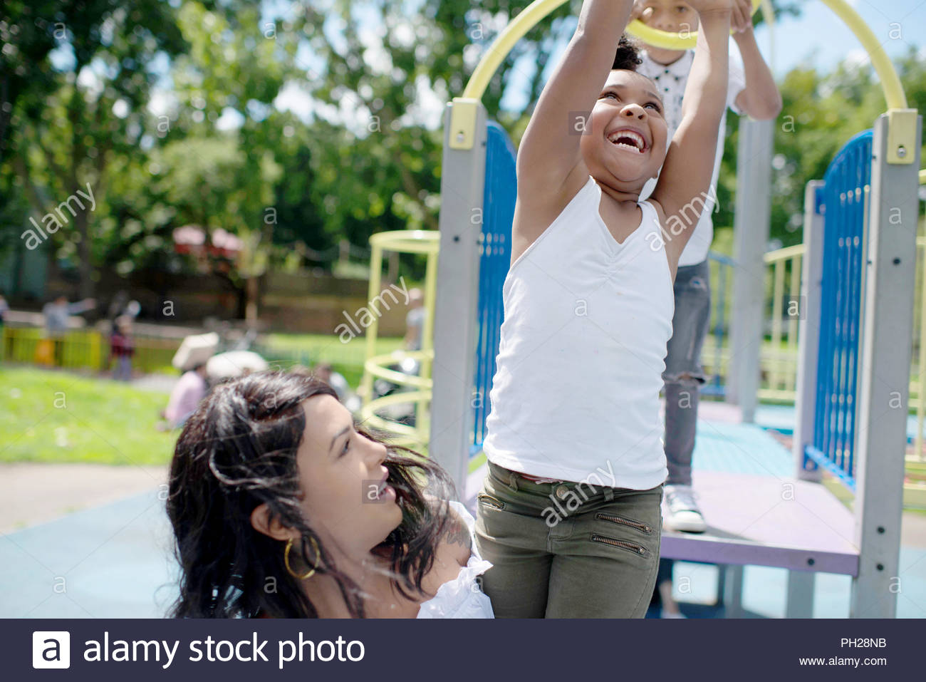 Mother and daughter playing on playground - Stock Image