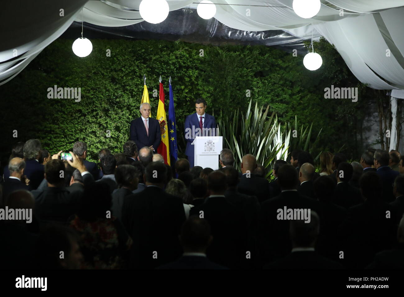Spanish Prime Minister Pedro Sanchez (C), accompanied by the Ambassador of Spain in Colombia, Pablo Gomez de Olea (L), delivers a speech during a meeting with the Spanish community residing in Colombia held at the Spanish embassy, in Bogota, Colombia, 29 August 2018. Sanchez arrived in Bogota today to meet tomorrow with the Colombian President Ivan Duque, on the third stop of his Latin American tour. EFE/J.J. Guillen - Stock Image