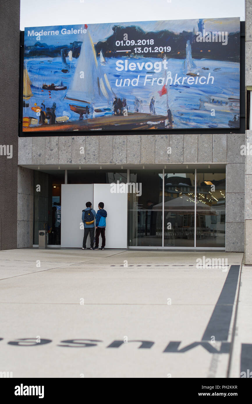 """30.08.2018, Saarland, Saarbrücken: A large poster above the entrance of the Modern Gallery advertises the exhibition """"Slevogt und Frankreich"""". On the occasion of Max Slevogt's 150th birthday, the Saarlandmuseum is showing a large exhibition of his works from 01.09.2018 to 13.01.2019. Photo: Oliver Dietze/dpa Stock Photo"""