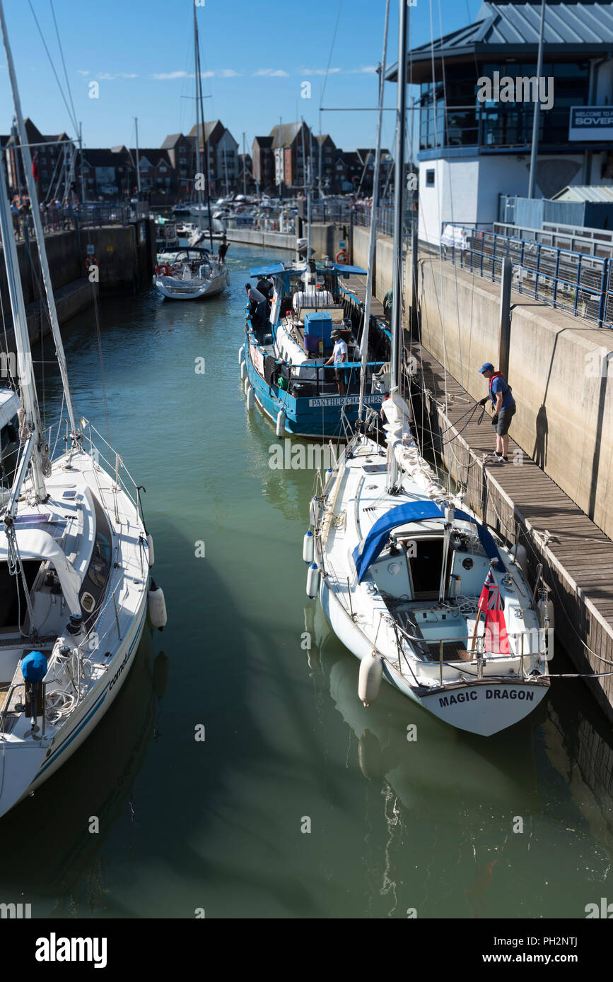 Small boats entering Sovereign Harbour via the lock gates in Eastbourne, East Sussex, England, UK. - Stock Image
