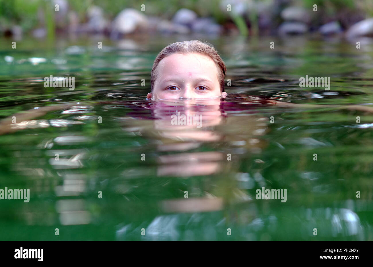 Girl half submerged swimming in a natural pool. Stock Photo