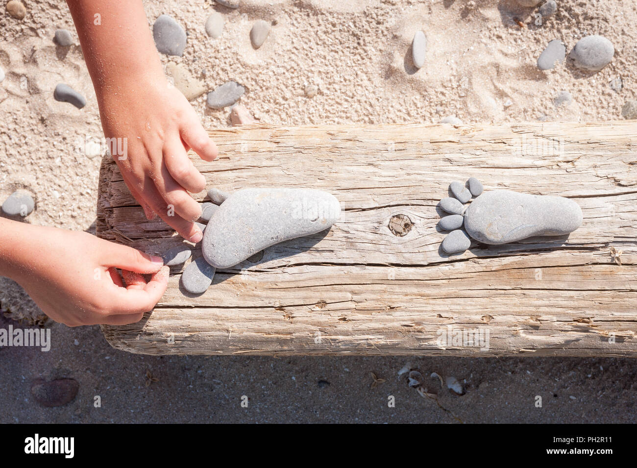 Child making little feet from pebbles, Sandbanks Provincial Park, Prince Edward County, Canada - Stock Image