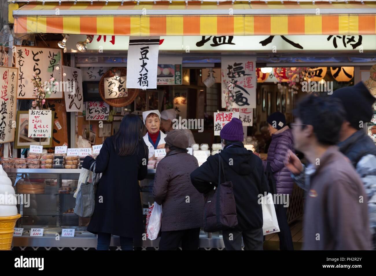 Customers waiting in line for Daifuku, a Japanese sweet, at the Jizo-Dori Shopping Street, Sugamo, Tokyo, Japan, December 13, 2017. () - Stock Image