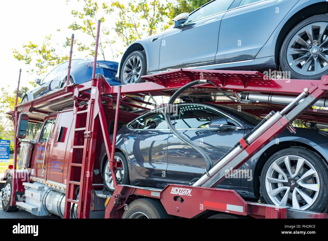 Brand new Tesla motors electric cars, including the Tesla Model 3 on a car carrier truck awaiting delivery near the company's headquarters and factory in the Silicon Valley, Fremont, California, July 28, 2018. () - Stock Image