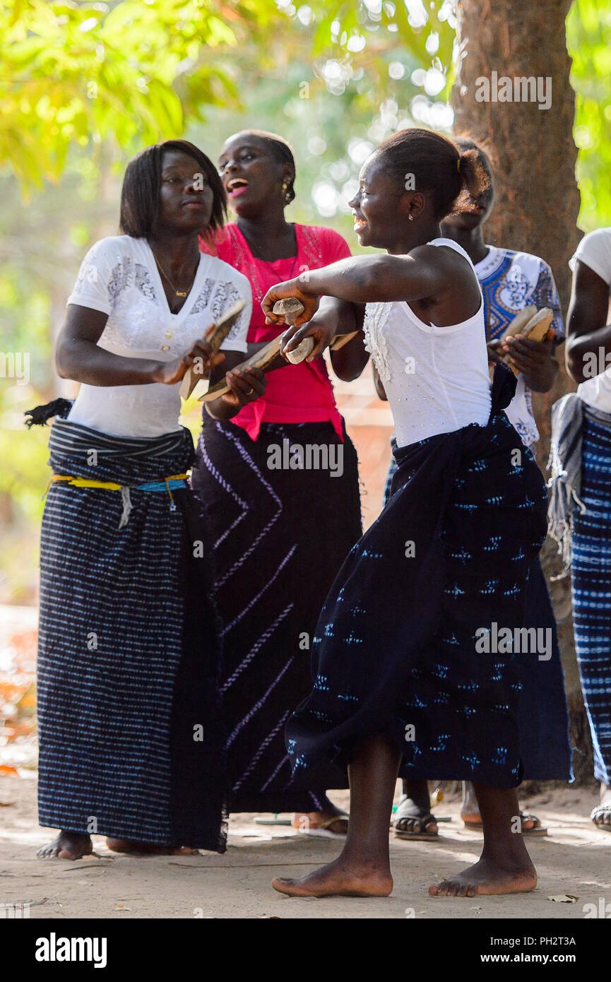Kaguit vil., SENEGAL - APR 30, 2017: Unidentified Diola women in shirts and skirts hold a special attributes during a traditional dance Kumpo in a Sac - Stock Image