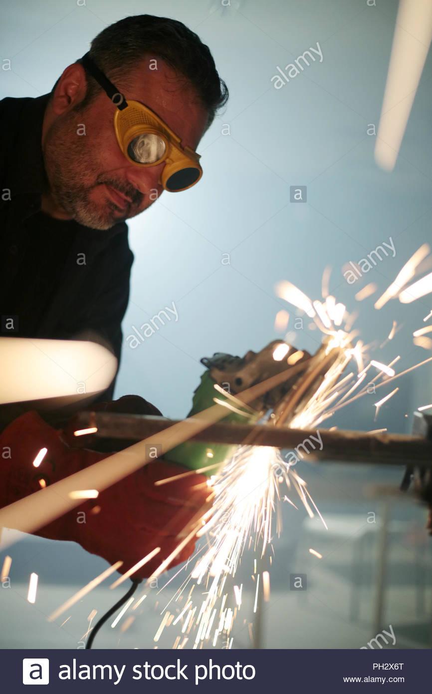 Worker grinding iron metal - Stock Image