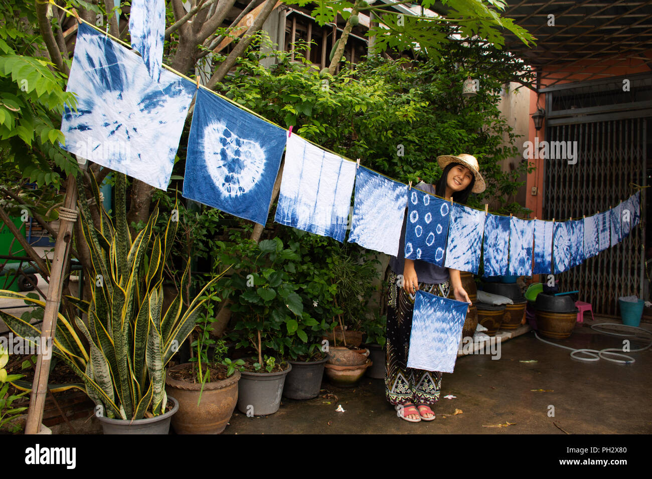 b9582f4149ac Thai women tie batik dyeing handkerchief tie batik indigo color or mauhom  color and hanging process dry clothes in the sun at garden outdoor in Nontha