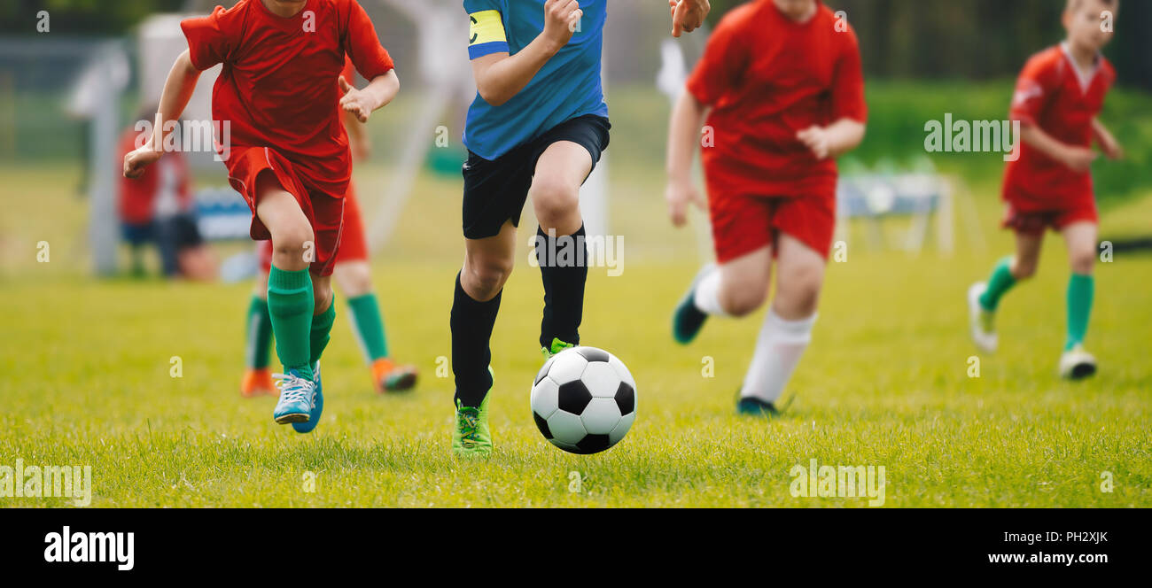Running Soccer Football Players. Footballers Kicking Football Match. Soccer School Tournament. Young Soccer Players Running After the Ball. - Stock Image
