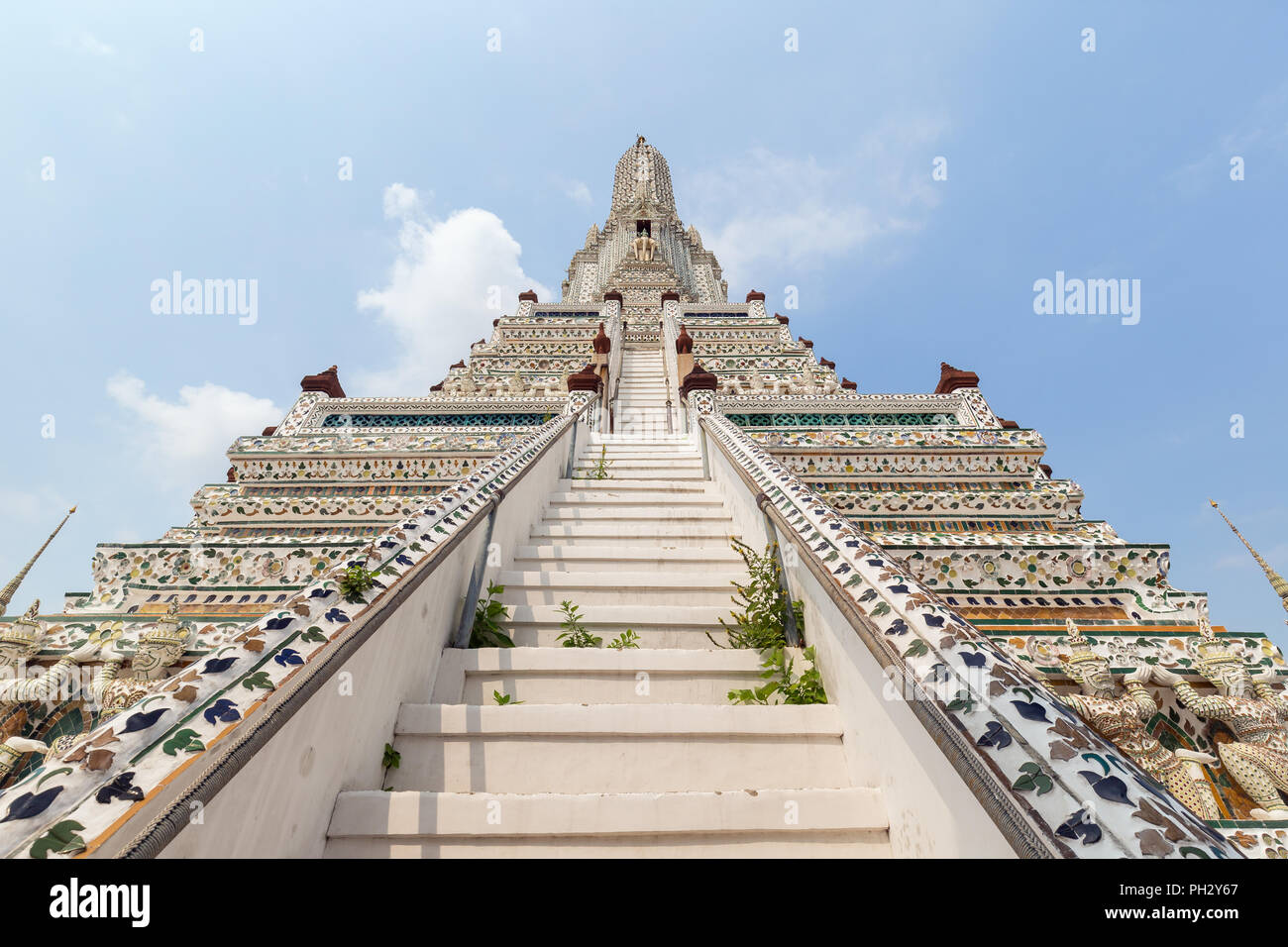 Front and low angle view of decorated Wat Arun temple in Bangkok, Thailand, on a sunny day. - Stock Image