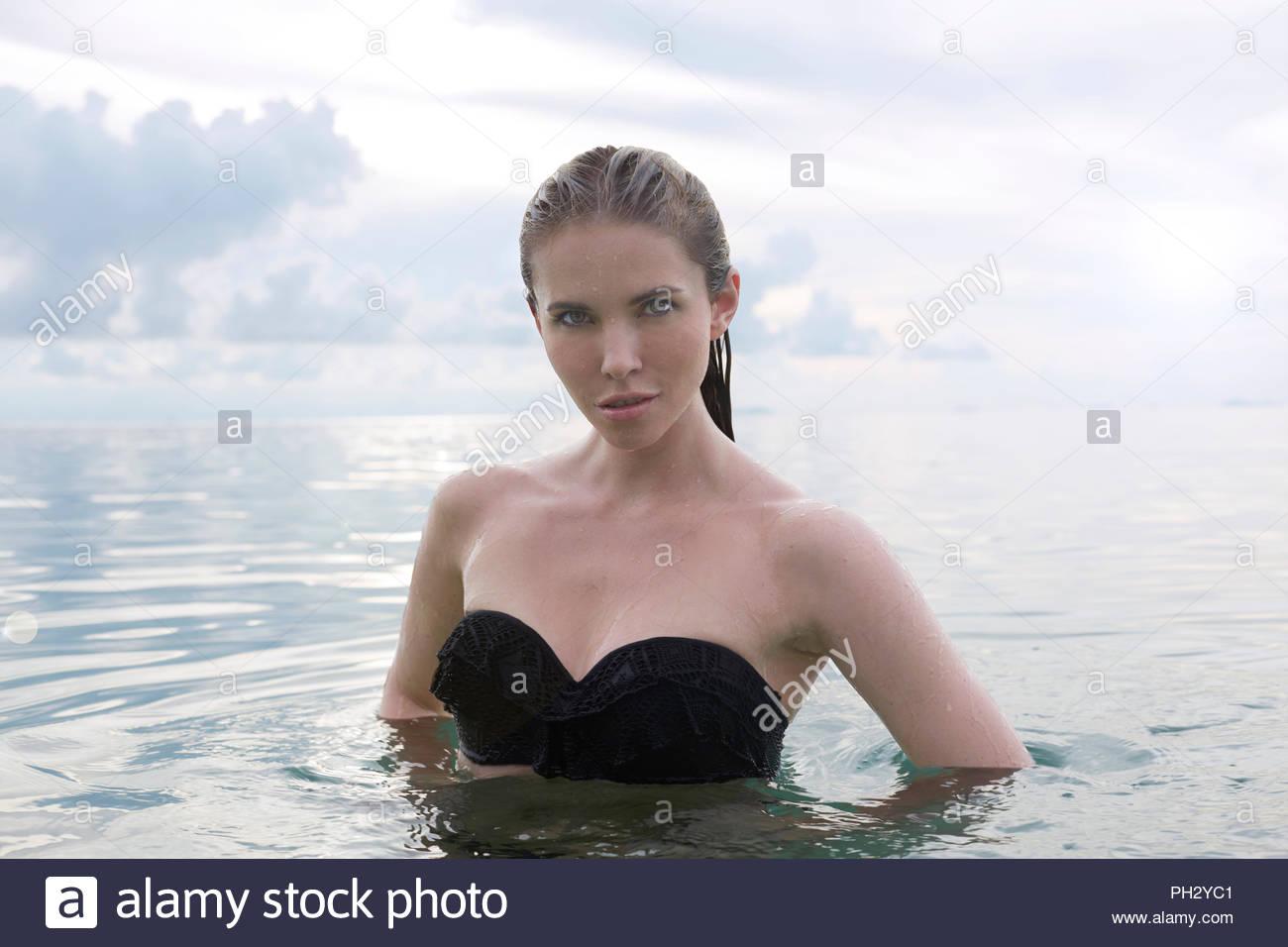 Young woman wearing black bikini standing in sea Stock Photo