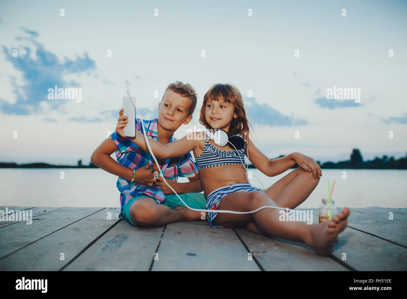 Portrait of positive children playing with mobile phones together on a wooden pier. Making selfie. - Stock Image