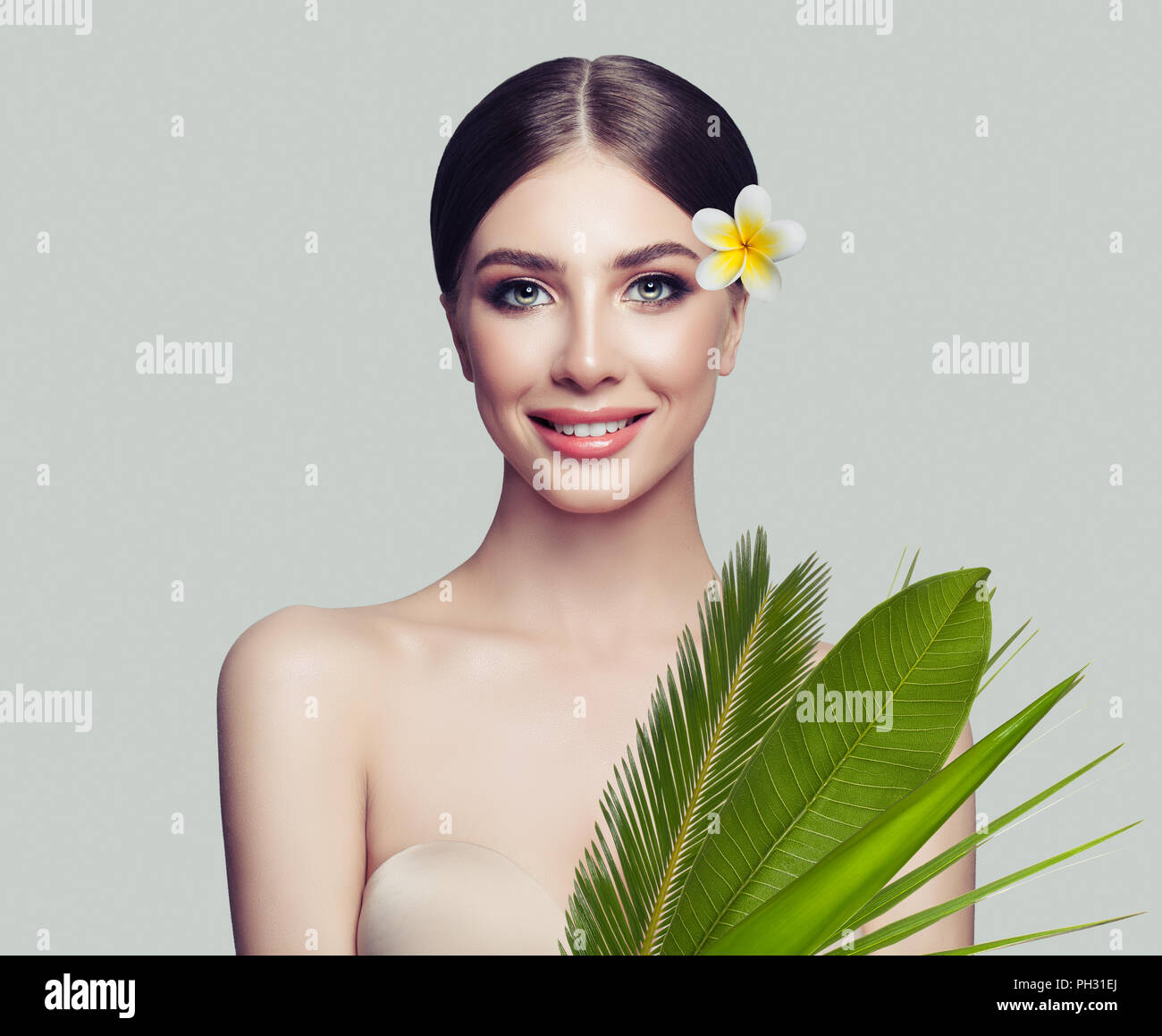 Spa woman with healthy skin, cute smile and tropical leaves and flowers on white background, spa beauty and cosmetology concept - Stock Image
