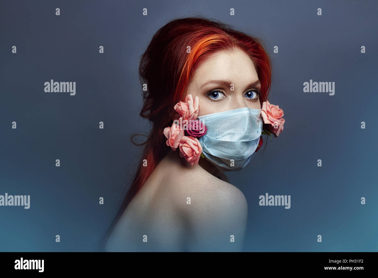 Art fashion redhead woman with medical respirator on her face, rose flowers grow from under mask, clean air lack of oxygen, bad ecology and dirty air. - Stock Image