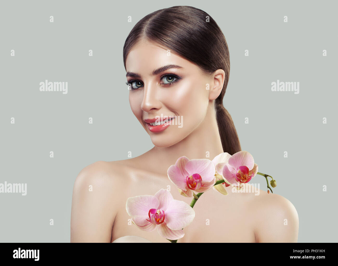 Cute smiling woman with healthy skin and pink orchid flowers. Facial treatment, cosmetology, beauty salon, skin care and spa concept - Stock Image
