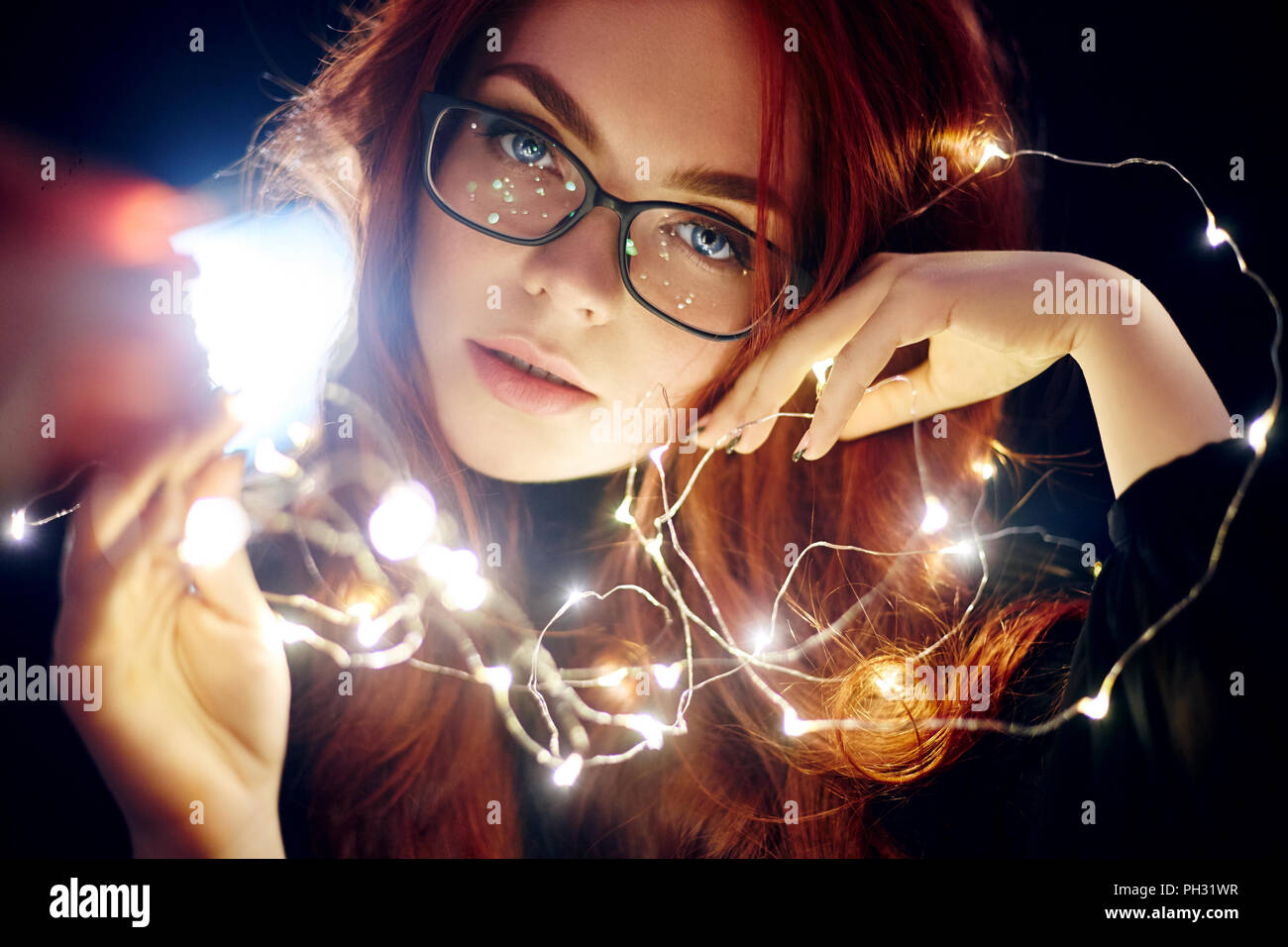 7bde57e687 Art portrait of a woman with red hair in Christmas lights. Girl in glasses  with