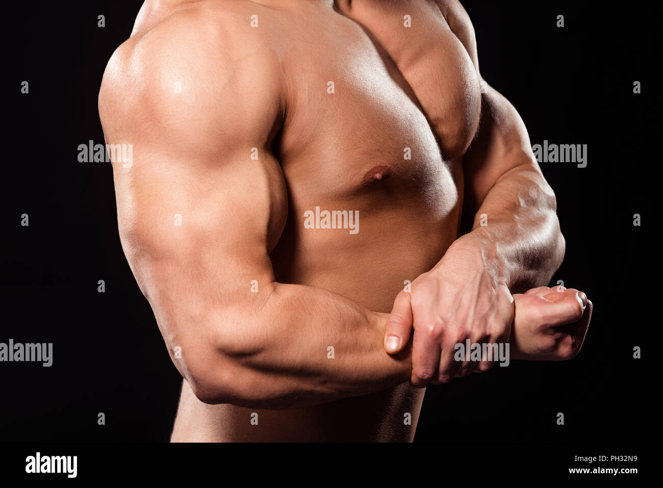 Close-up of bodybuilder flexing bicep. - Stock Image