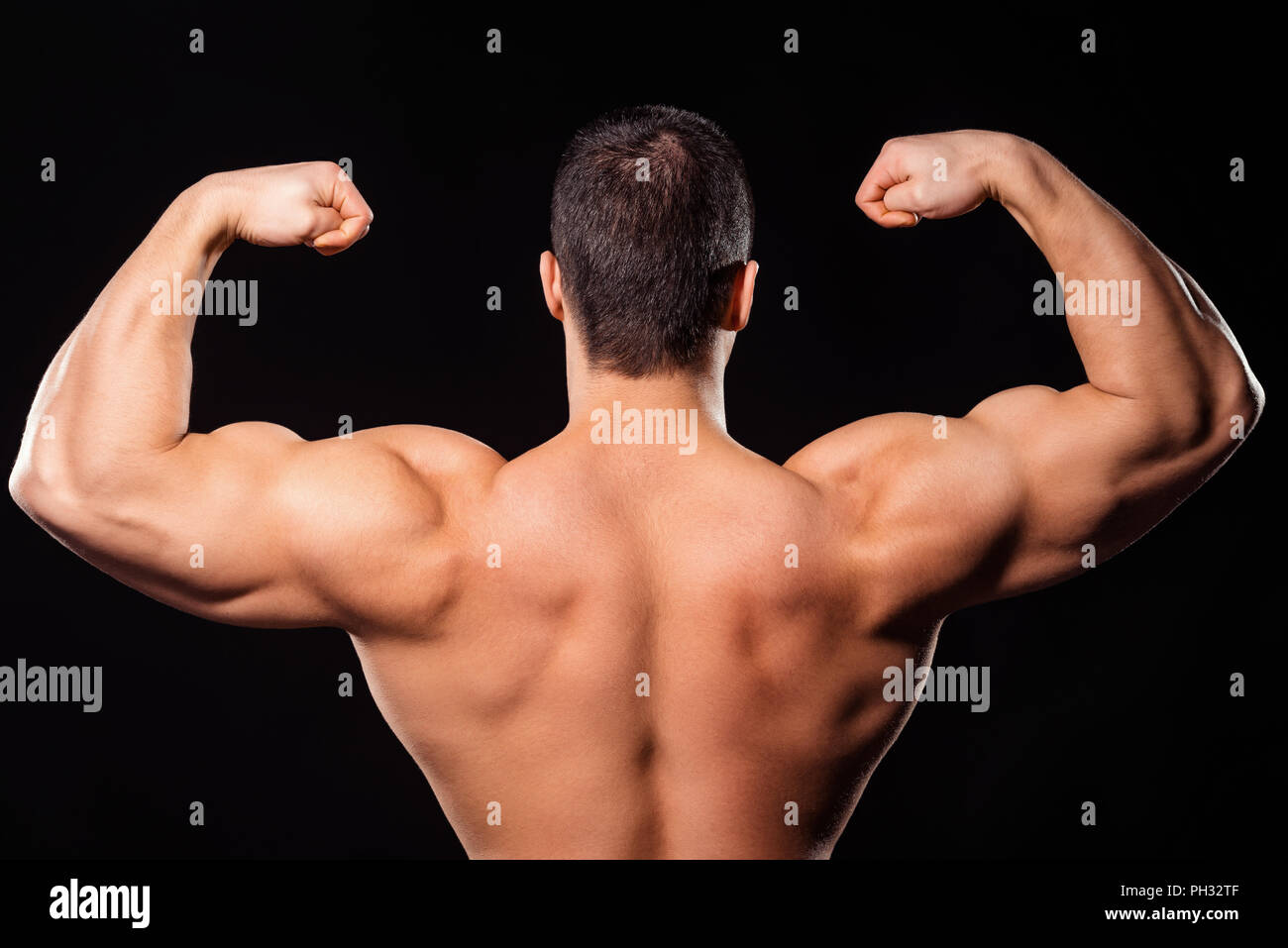 Men's rear double biceps pose. Bodybuilder's rear double biceps pose. Upper back and arms. So close to winning. Stock Photo