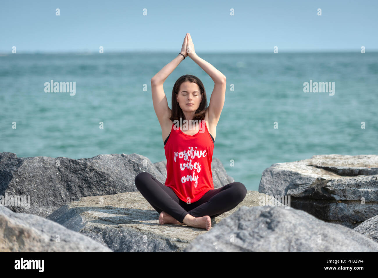 woman sitting crossed legged on rocks practicing yoga, easy pose, wearing a t shirt with 'Positive vibes only' slogan. - Stock Image