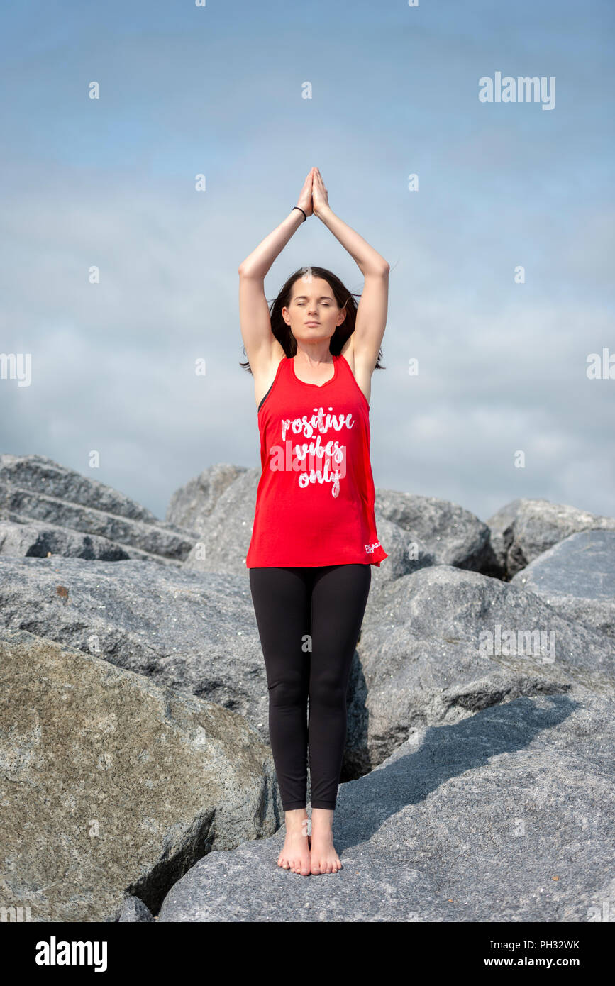 woman standing doing yoga, mountain pose, wearing a t shirt with 'positive vibes only' slogan. - Stock Image
