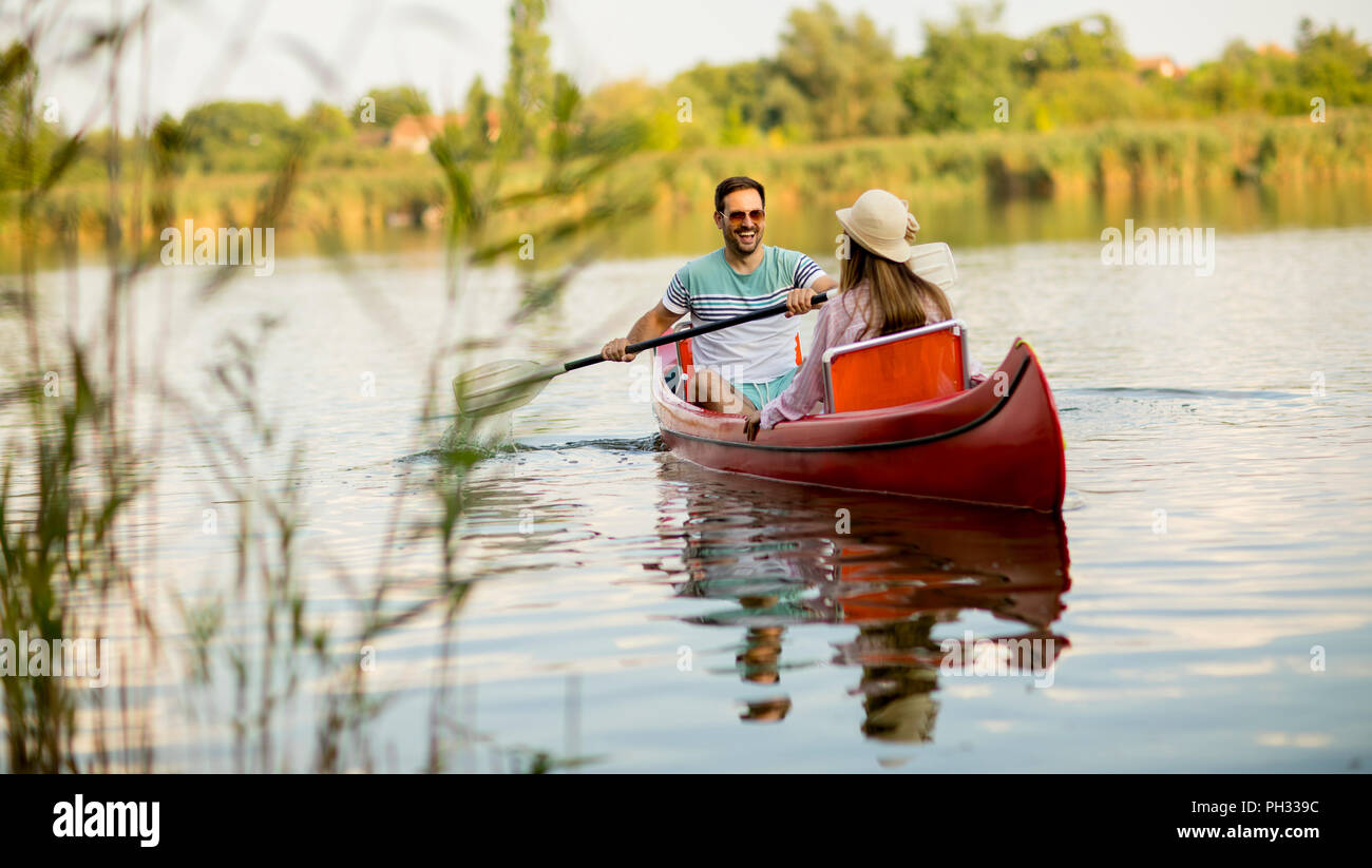Loving couple rowing on the lake at summer day - Stock Image