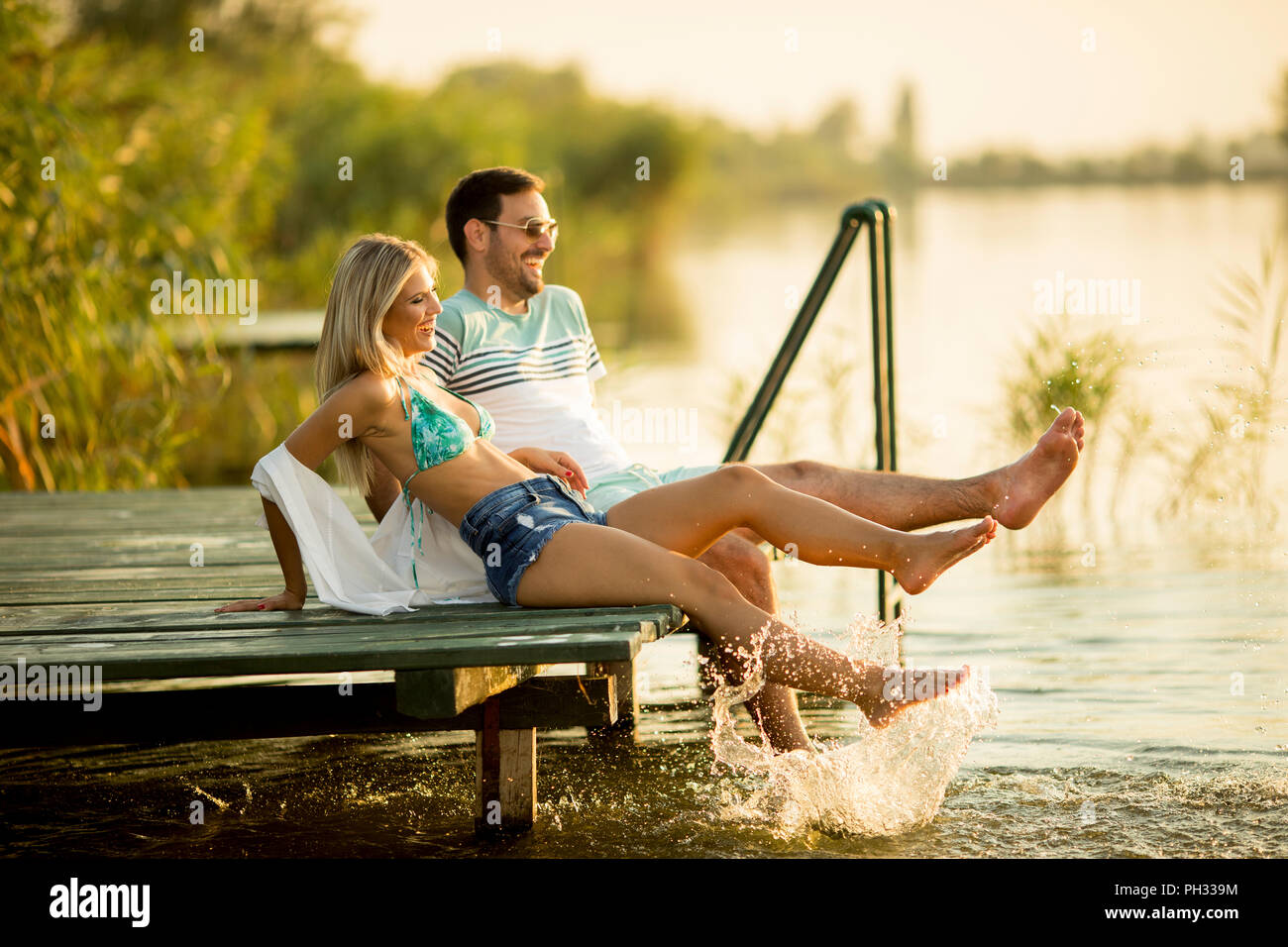 Romantic couple sitting on the wooden pier on the lake at sunny day - Stock Image