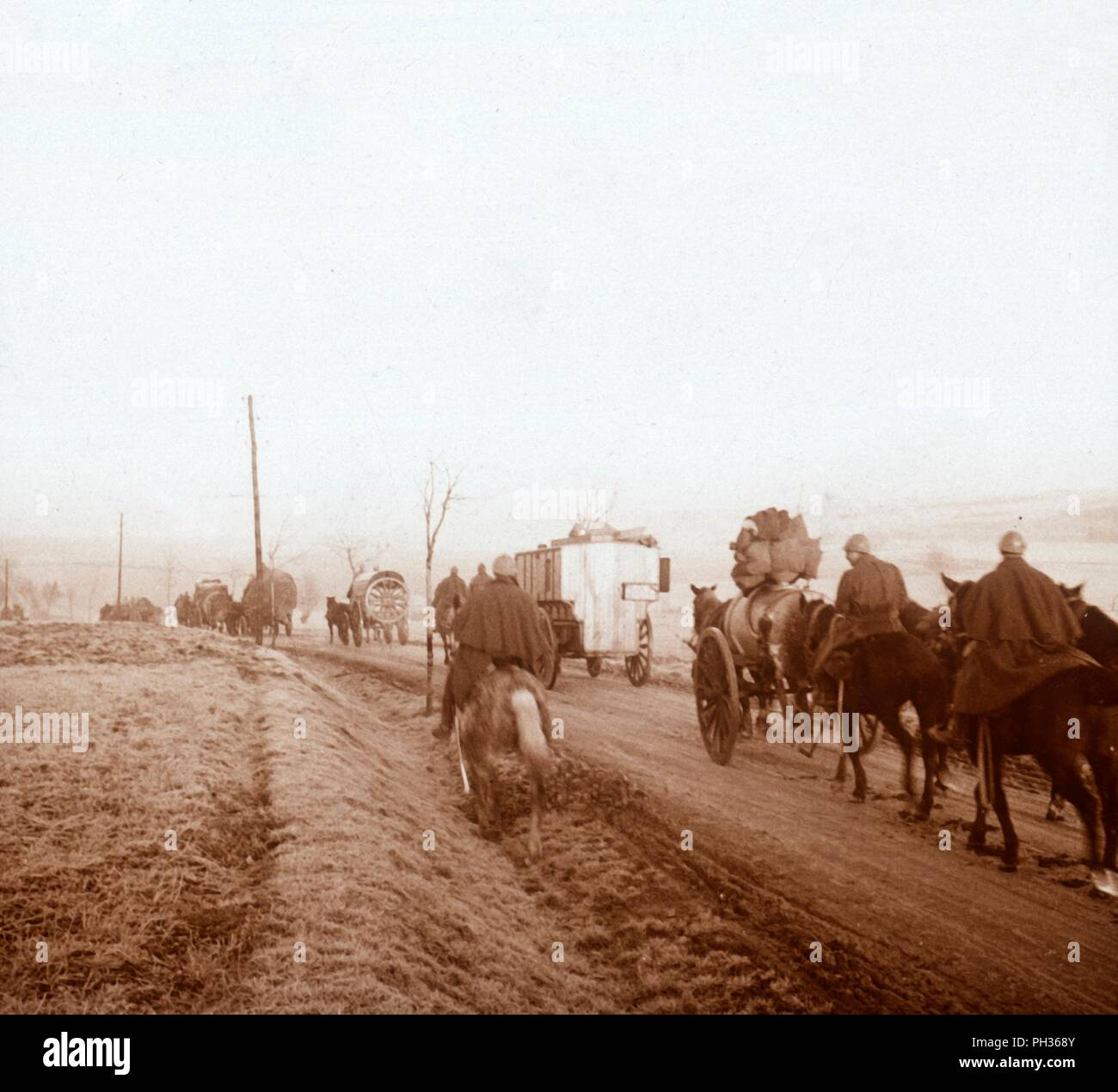 Convoy, Genicourt, northern France, 1916. A French Army re-supply convoy makes its way along the main road through the small Lorraine township of Genicourt-Sur-Meuse, on it's way to the front line at Verdun in the winter of 1916. The convoy consists of horse-drawn wagons bringing a variety of goods to the beleaguered French garrisons at the Verdun fortresses. A squadron of Chasseurs-au-Cheval (Light Cavalry) act as a cavalry screen for the convoy. Photograph from a series of glass plate stereoview images depicting scenes from World War I (1914-1918). - Stock Image