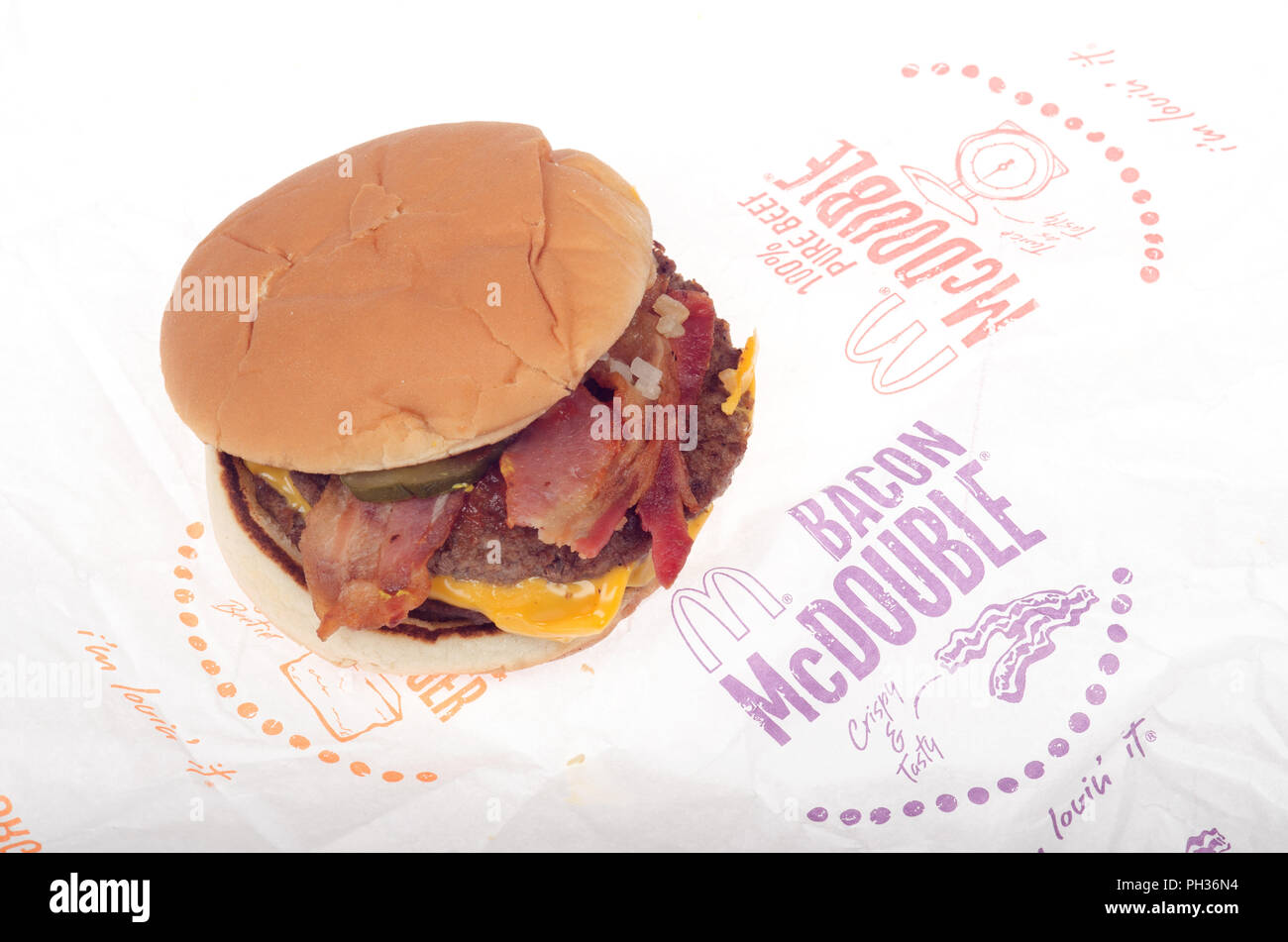 McDonalds Bacon McDouble Cheeseburger with ketchup, onions, pickle and yellow cheese on wrapper - Stock Image
