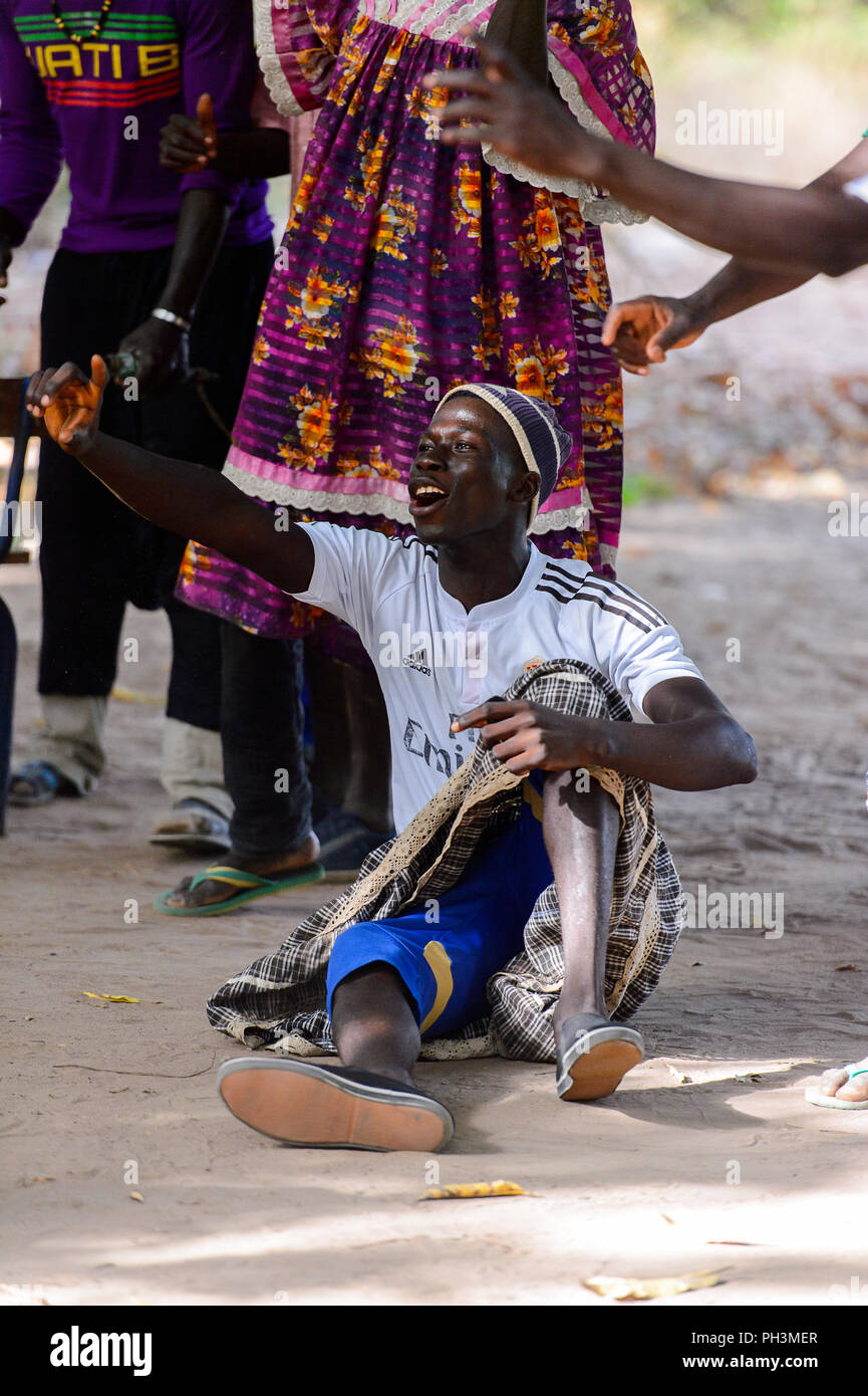Kaguit vil., SENEGAL - APR 30, 2017: Unidentified Diola man sits on the groung and raises his hand during a traditional dance Kumpo in a Sacred Forest - Stock Image