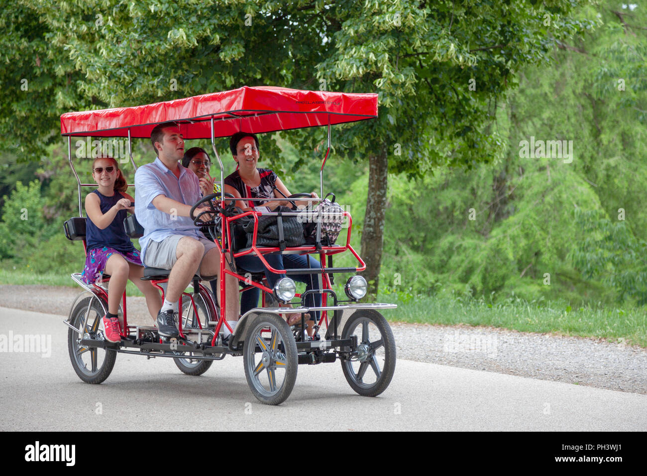 On the ramparts at Lucca (Tuscany - Italy),  a tourist family having a drive in a four-wheeled pedal car under the shade of hundred-year old trees. - Stock Image
