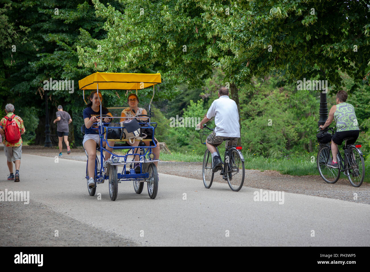 On the ramparts at Lucca (Tuscany - Italy),  tourists having a drive in a four-wheeled pedal car under the shade of hundred-year old trees. - Stock Image