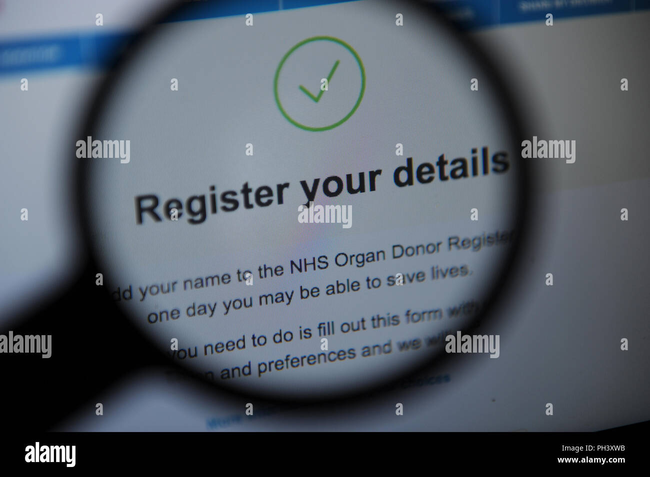 The NHS Organ Donor Register online seen through a magnifying glass - Stock Image