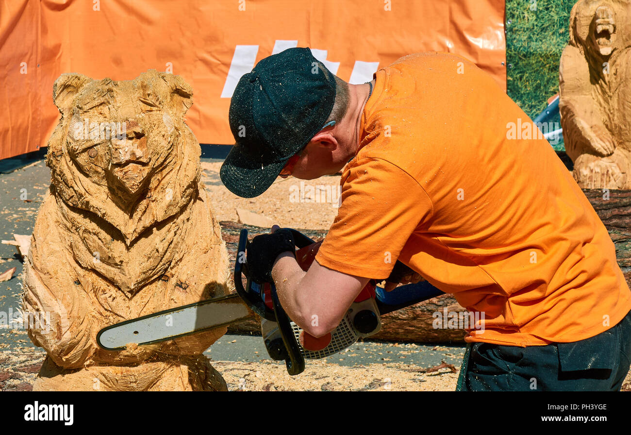 Experienced carpenter making a big wooden bear sculpture with a chainsaw during a local competition, almost finished Stock Photo