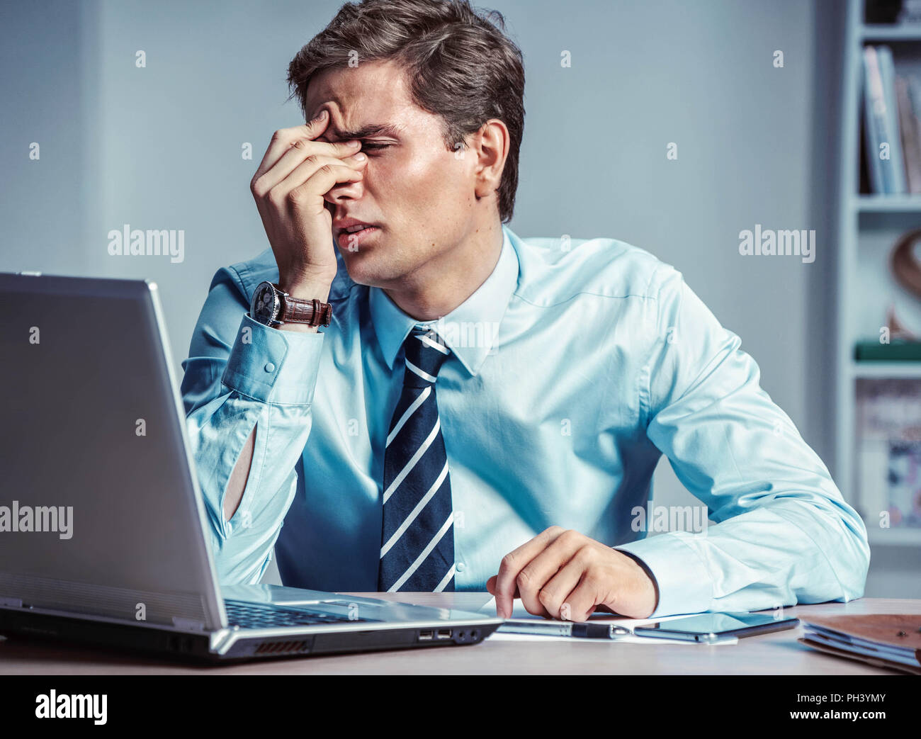 Young office man with pain in his head or an eye. Photo of man suffering from stress or a headache grimacing in pain. Business concept - Stock Image
