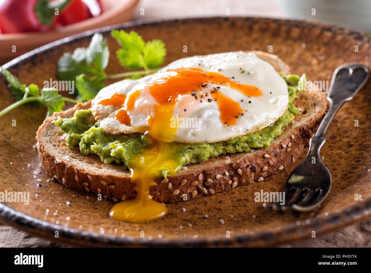 A slice of toast with delicious avocado, fried egg and hot sauce. - Stock Image