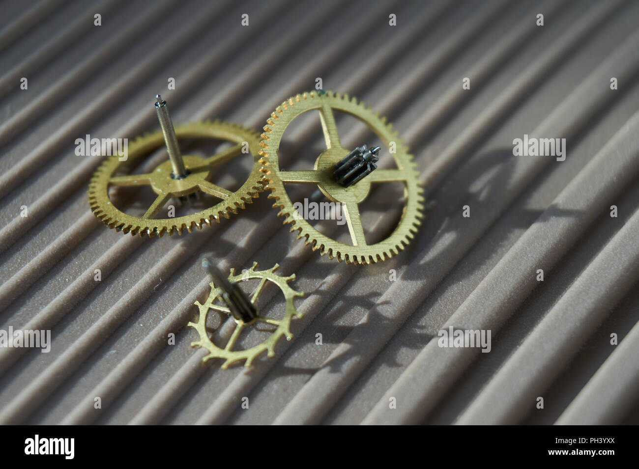Three different precision engineered toothed brass metal cog wheels lying on a ridges grey background with copy space in a conceptual image - Stock Image