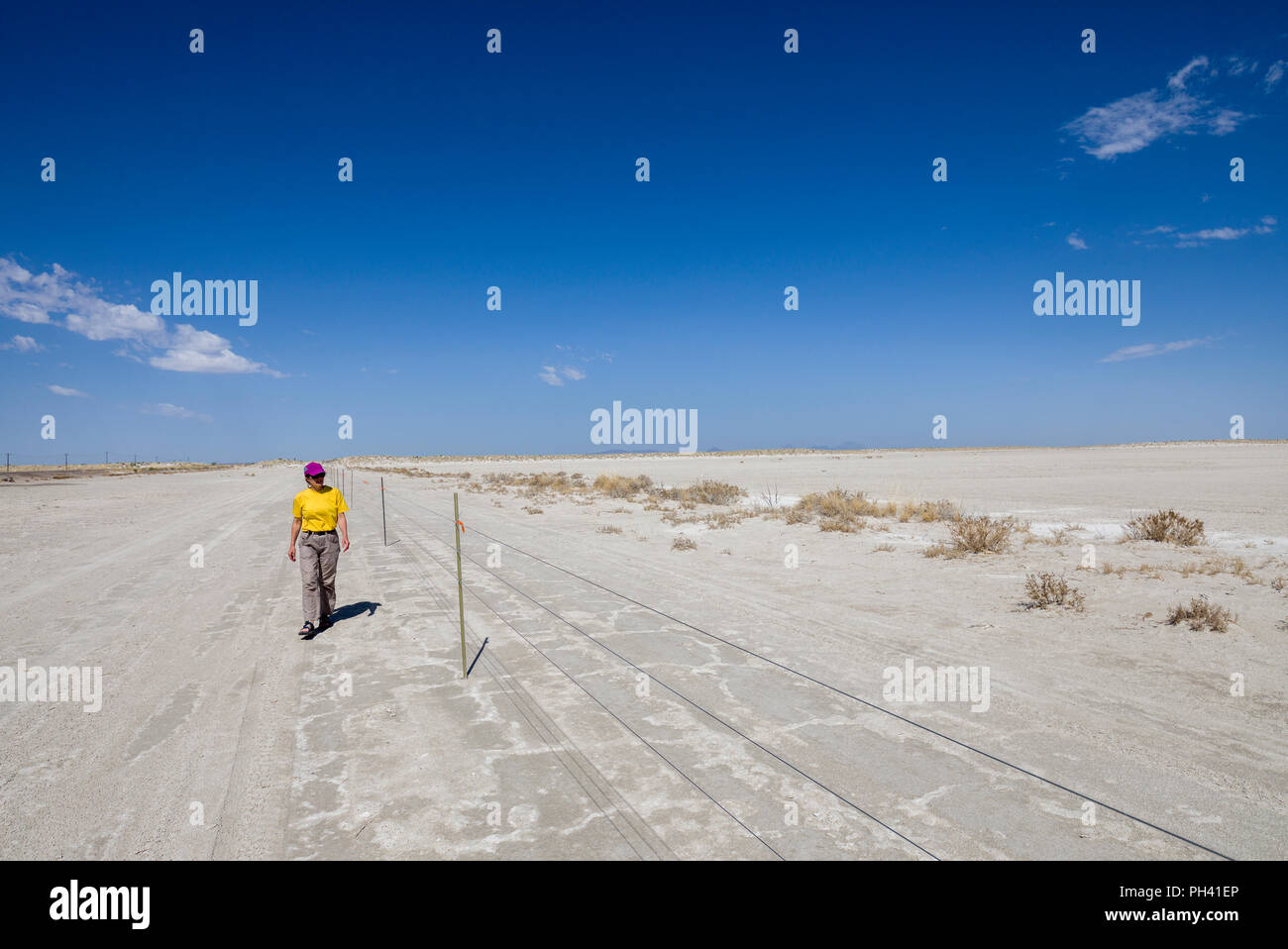 Woman walking alongside an electric fence in the Chihuahuan desert, New Mexico, USA Stock Photo