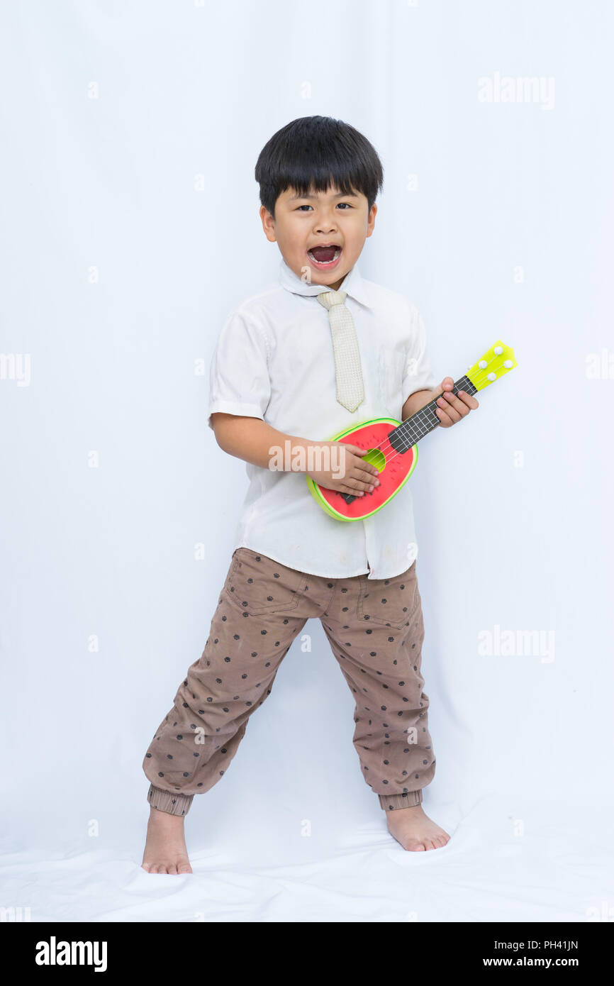Cute Asian boy holding guitar on white background, portrait boy Open your mouth, Stock Photo
