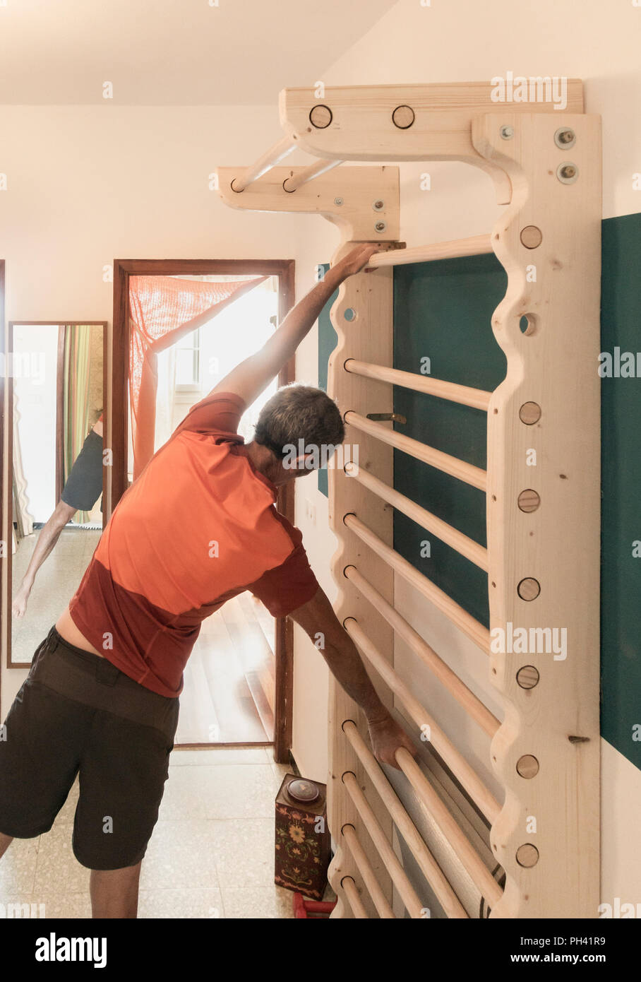 Mature man exercising at home on homemade wall bars in small