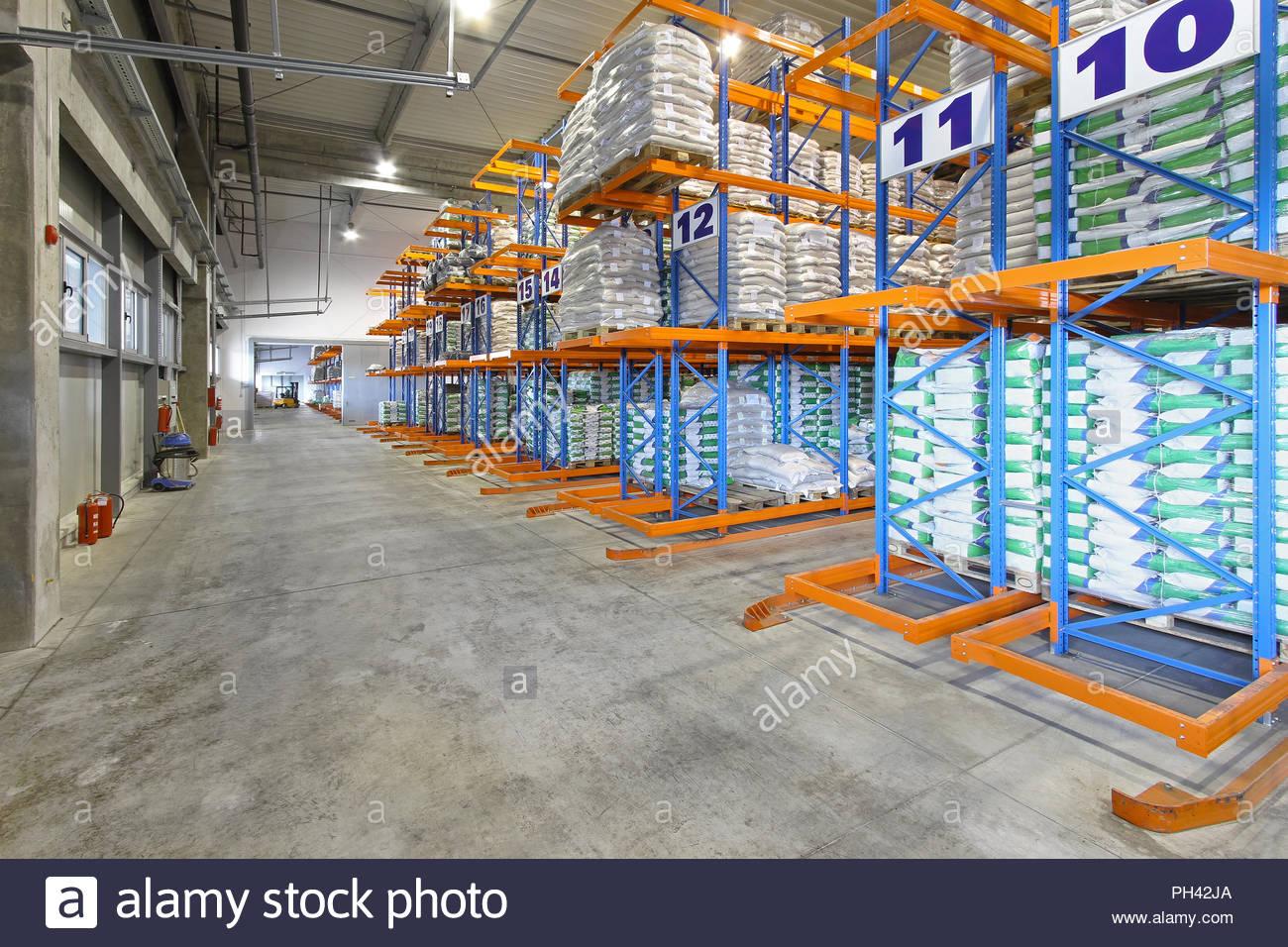 Big distribution warehouse with sacks at shelves - Stock Image
