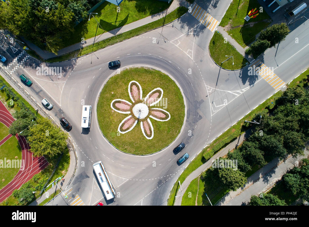 Top view of the road with a circular motion and a flower bed. Aerial photography. - Stock Image