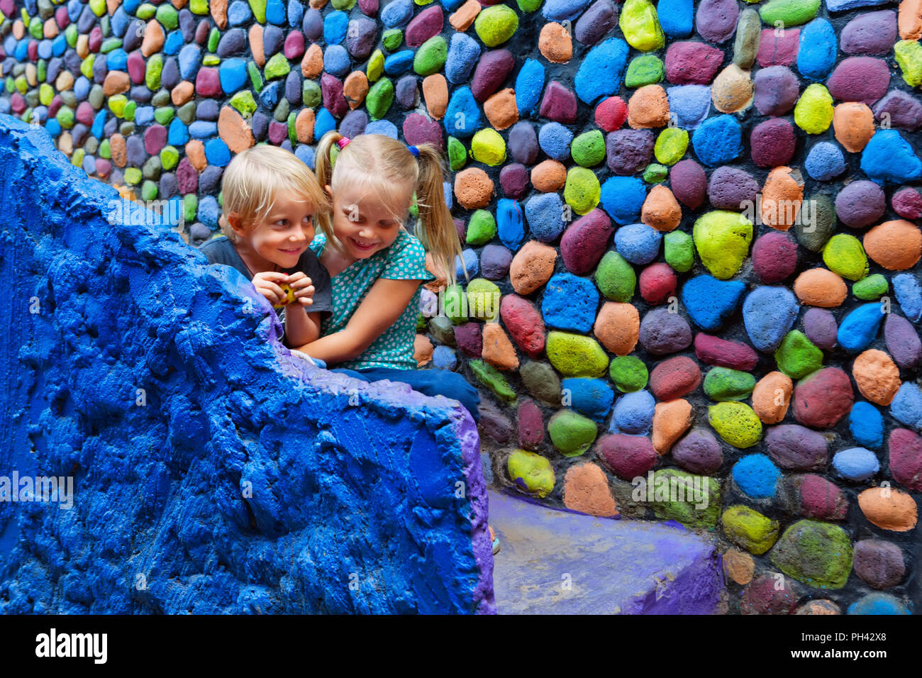 Two happy kids have fun together sitting outside home on colorful stone steps. Playful girl hug laughing younger brother. Travel lifestyle, walking ci - Stock Image