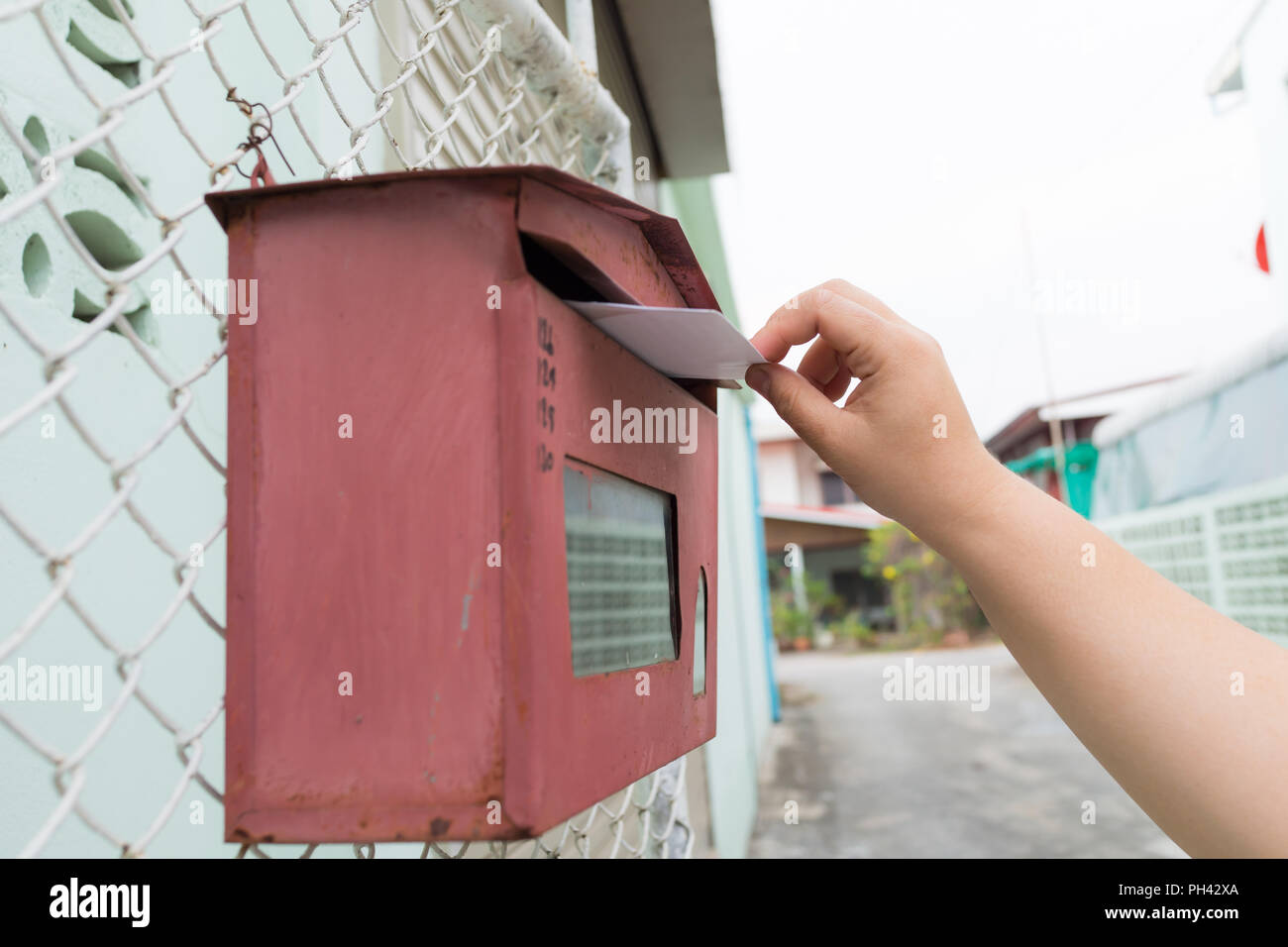 posting a letter to red british postbox on street, Closeup on a woman's hand as she is posting a letter, - Stock Image