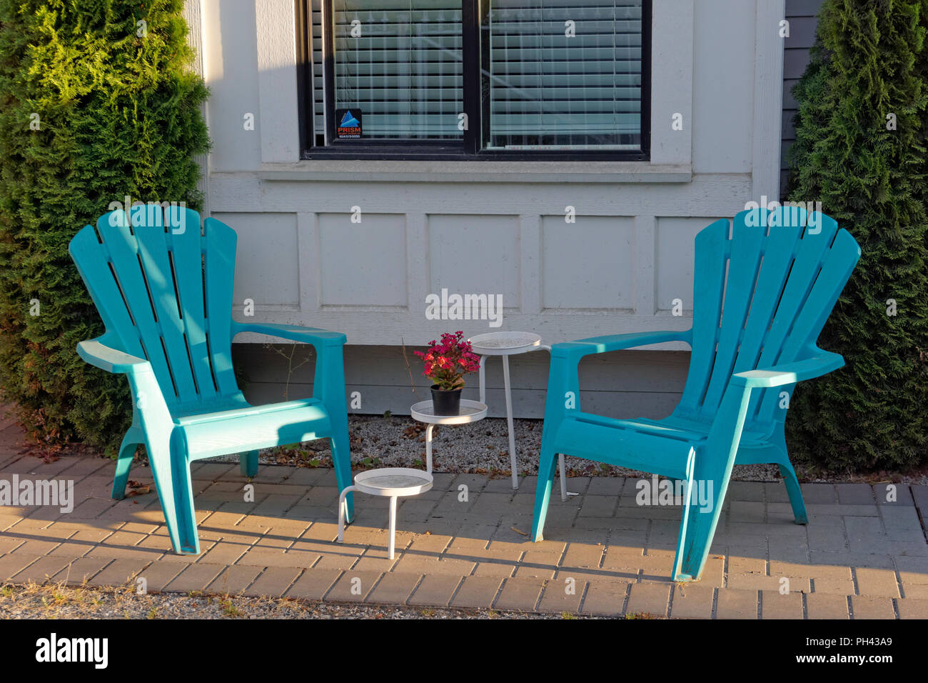 Two Plastic Adirondack Chairs On A Summer Patio Outside A House